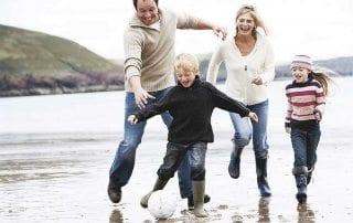 Dollende familie dollend op het strand