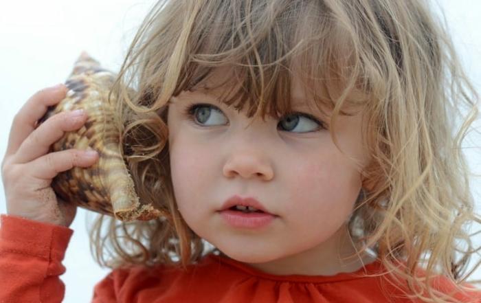 kind aandachtig luisterend in schelp
