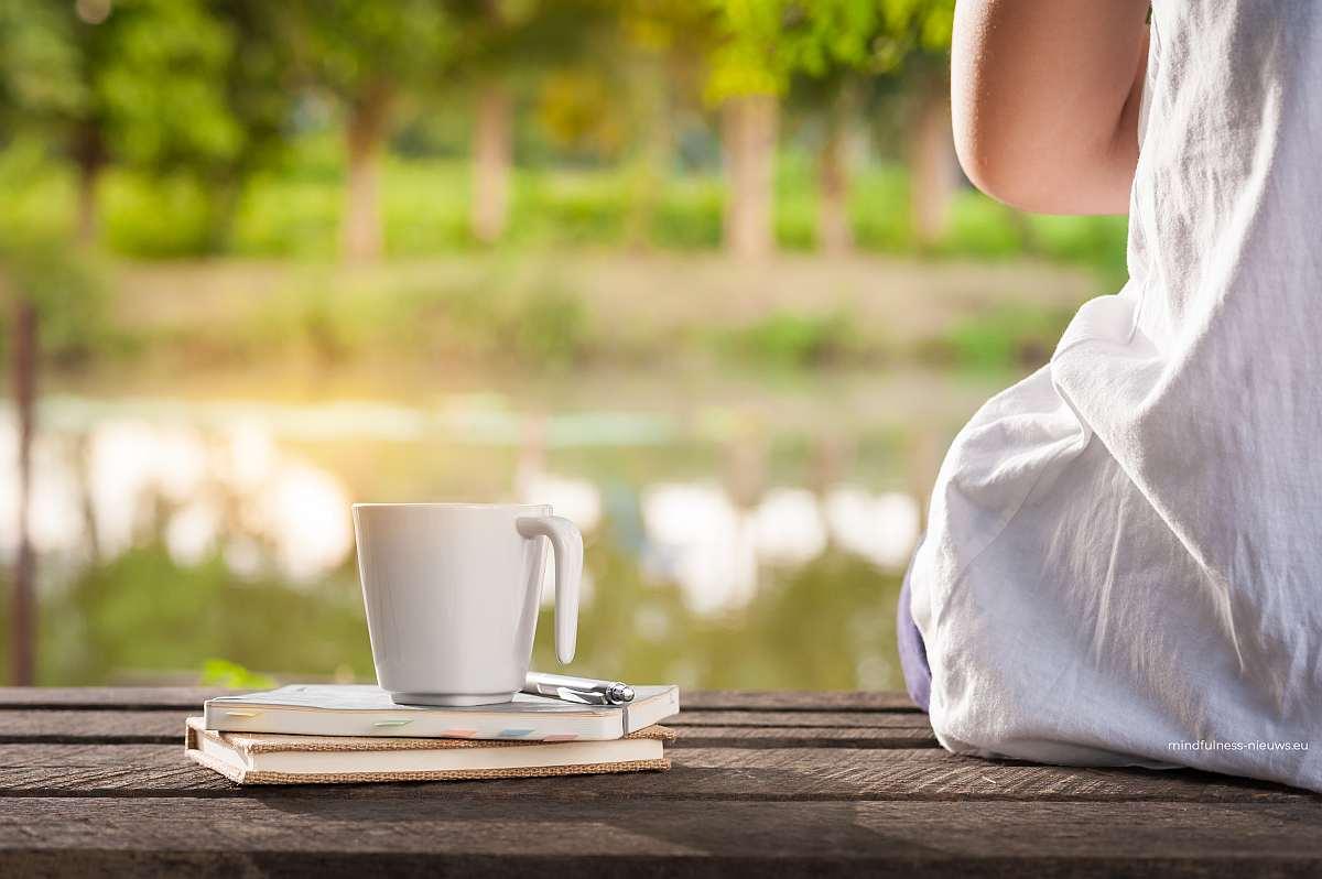 rust uitstralende foto van meisje op houten steiger met boeken en kop koffie of thee uitkijkend op een water