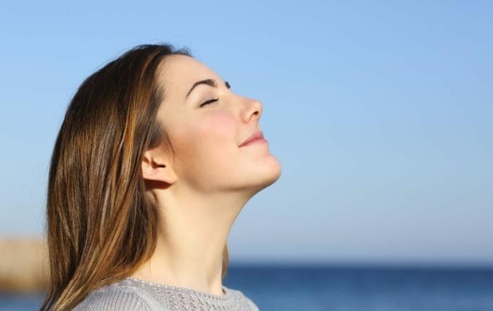 vrouw ademt aan zee